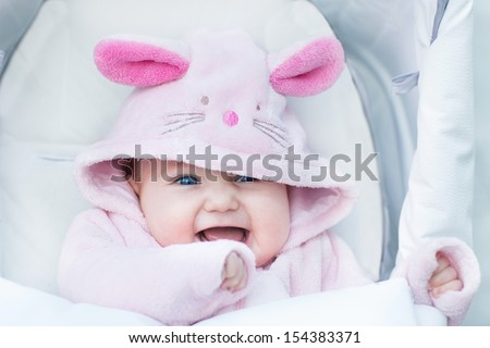 Adorable funny baby girl sitting in a stroller in a bunny snow suit on a walk in a cold winter park - stock photo