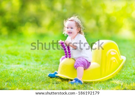 Adorable funny curly toddler girl playing in the garden, enjoying a swing ride, playing with plastic toys on the lawn on a sunny summer morning - stock photo