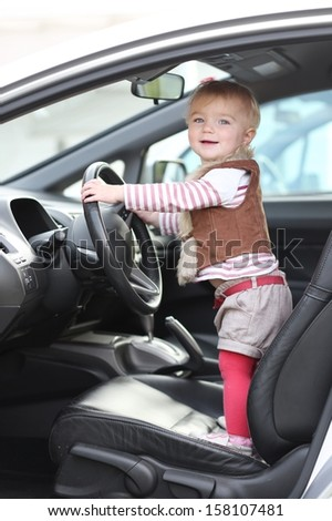 Adorable funny little baby girl stands inside of the car on driver seat holding steering wheel  - stock photo