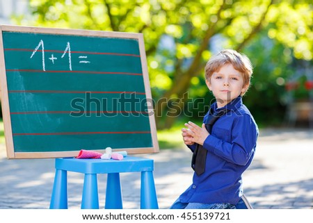 Adorable funny little kid boy at blackboard practicing counting and math, outdoor school or nursery. Child having fun with learning. Back to school concept. - stock photo
