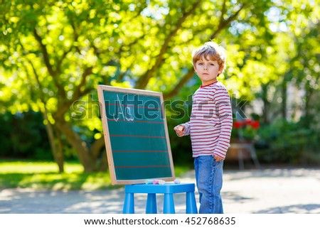 Adorable funny little kid boy at blackboard practicing writing letters, outdoor school or nursery. Child having fun with learning. Back to school concept. - stock photo