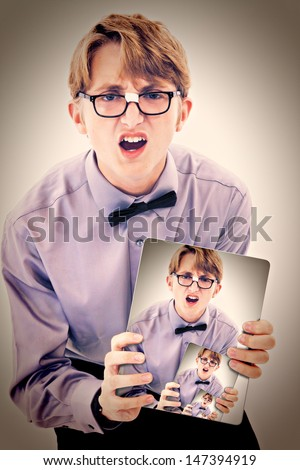 Adorable geeky teen boy holding electric notepad with photo of self. - stock photo