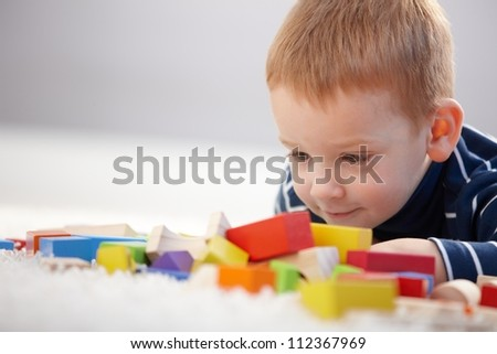 Adorable ginger-haired little boy playing with cubes, smiling. - stock photo