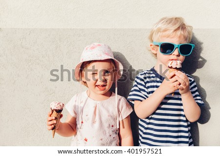 Adorable girl and boy eating ice cream - stock photo