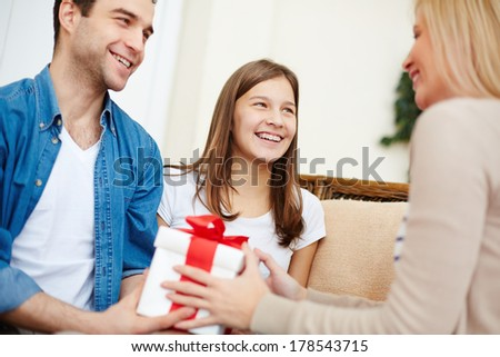 Adorable girl and her father giving present to blond female - stock photo