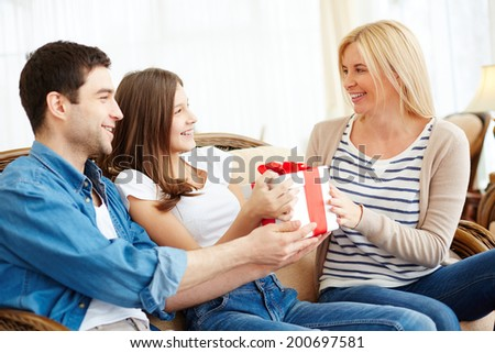 Adorable girl and her father giving present to happy woman - stock photo