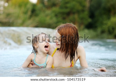 Adorable girl and her mom on a beach - stock photo