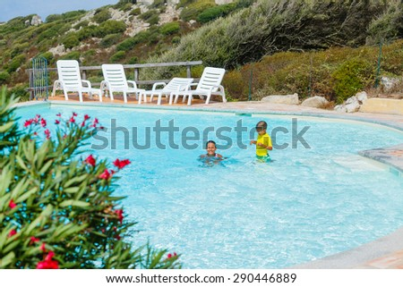 Adorable girl and little boy relaxing at swimming pool - stock photo