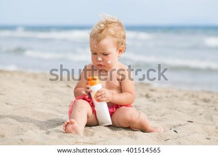 Adorable girl at beach applying sunblock cream, portrair - stock photo