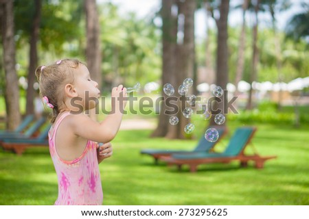 Adorable girl blow soap bubbles in park on the beach - stock photo