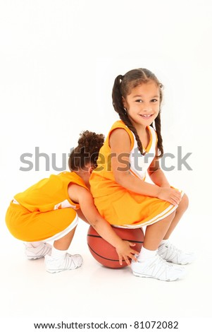 Adorable girl child and toddler basketball players in uniform over white.