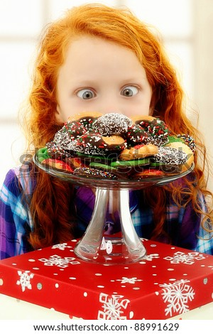 Adorable girl child excited about a tray of holiday Christmas cookies. - stock photo