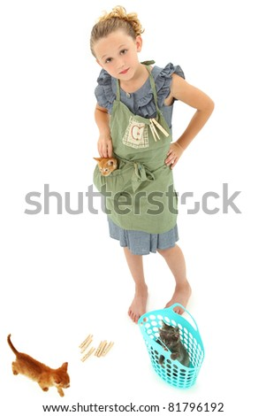 Adorable Girl Child in Apron playing house homemaker with kittens.  Retro dress and apron over white background. - stock photo