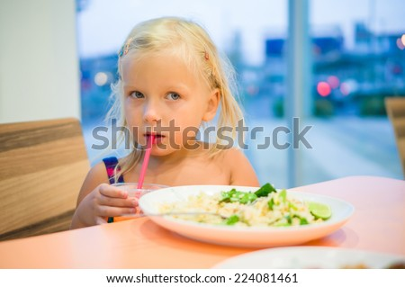Adorable girl dinning on food court with vegetables rice and juicy drink with straw - stock photo