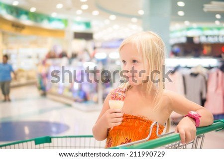 Adorable girl eat fruit ice cream with rainbow sprinkles in shopping cart in supermarket
