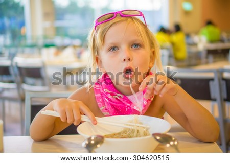 Adorable girl eat noodle soup on food court in mall - stock photo