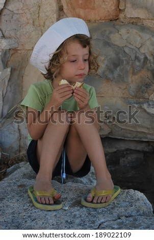 Adorable girl eating sandwich in nature - stock photo
