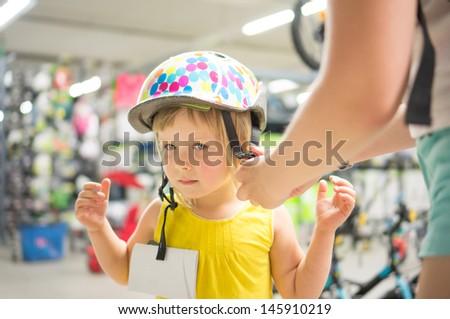 Adorable girl fitting bike helmet in sport store - stock photo