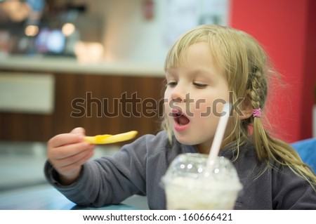Adorable girl have meal in fast food restaurant - stock photo