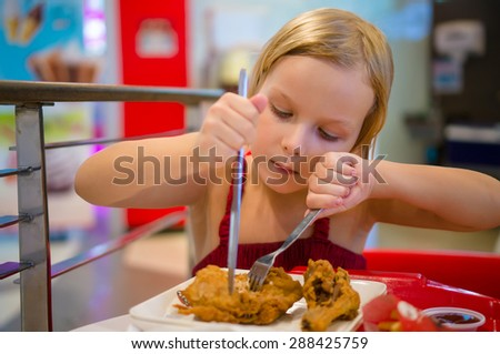 Adorable girl have meal with chicken,  soda drink and fried potatoes at fast food restaurant - stock photo