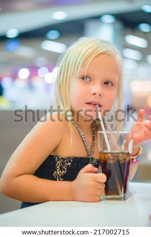 Adorable girl have meal with soda drink and fried potatoes at fast food restaurant - stock photo