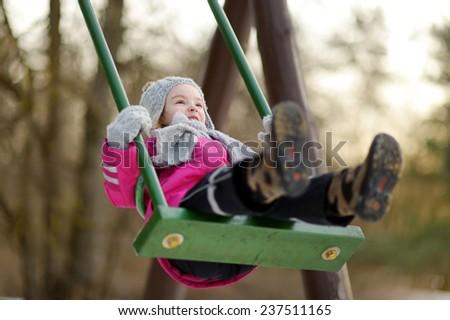 Adorable girl having fun on a swing on beautiful winter day - stock photo