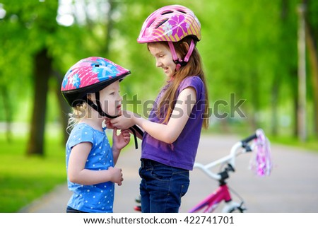 Adorable girl helping her little sister to put a bicycle helmet on - stock photo