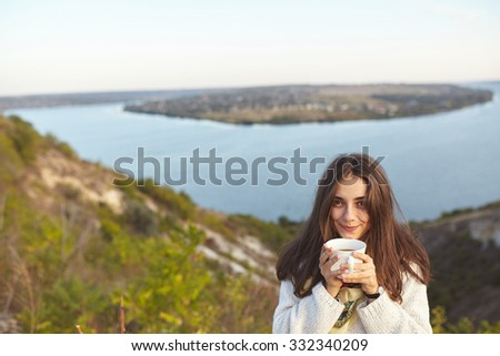 Adorable girl holding a cup of hot coffee outdoors in the morning. Shy young woman wearing sweater and holding a mug. - stock photo