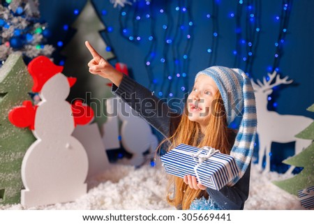 Adorable girl in a hat gnome with a gift in the snow points a finger toward   - stock photo