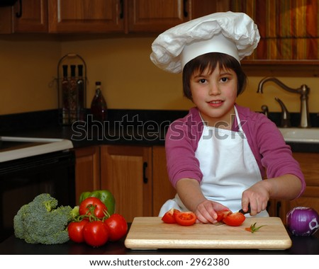 Adorable girl in apron and chef's hat slicing veggies for a pizza or salad. - stock photo