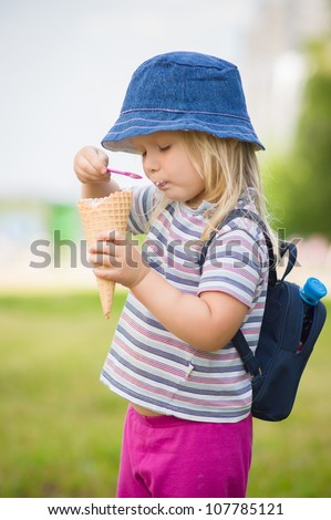 Adorable girl in blue hat eat ice cream - stock photo