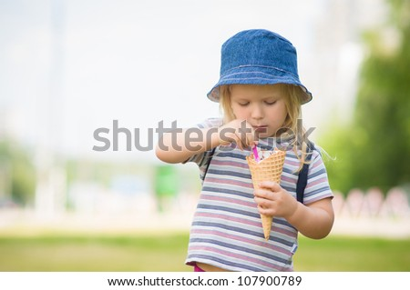 Adorable girl in blue hat eat ice cream