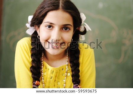 Adorable girl in front of classroom board - stock photo