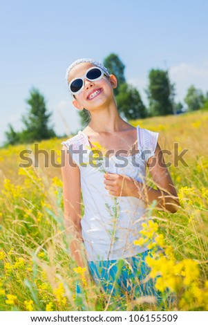 Adorable girl in glasses with flowers in yellow field. Summer freedom andjoy concept. Vertical view - stock photo