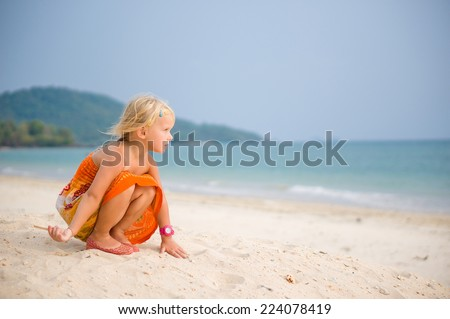 Adorable girl in orange dress play with sand on high sand ocean beach - stock photo