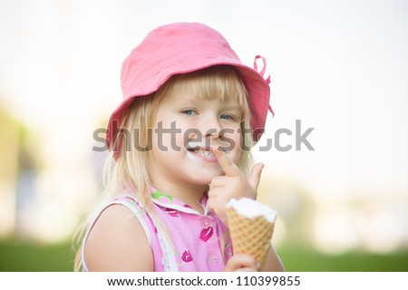 Adorable girl in pink hat eat ice cream sitting on grass - stock photo