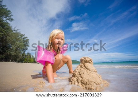 Adorable girl in pink swimming suit and inflatable arm bands build sand tower on ocean beach