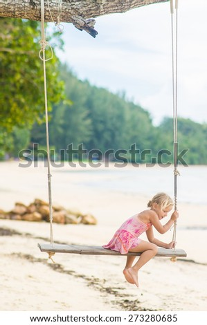 Adorable girl in pink swimming suit on swing on the beach - stock photo