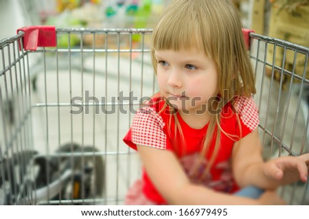 Adorable girl in red sit at shopping cart in supermarket - stock photo