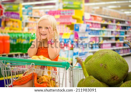Adorable girl in shopping cart looks at giant jack fruits on boxes in supermarket - stock photo