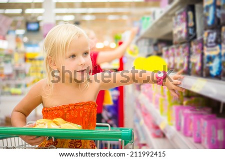 Adorable girl in shopping cart looks at goods on shelves in supermarket
