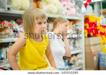 Adorable girl in shopping cart with mother on back select toys in supermarket - stock photo