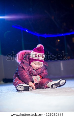 Adorable girl in skates sit on ice rink after fall in evening