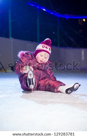 Adorable girl in skates sit on ice rink after fall in evening - stock photo