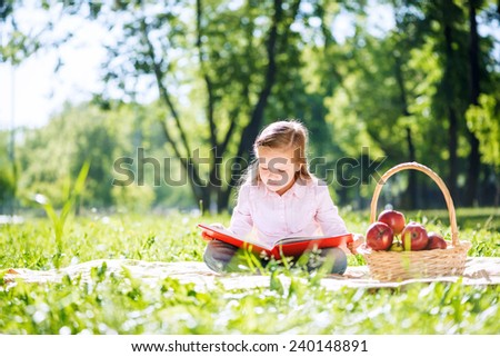 Adorable girl in summer park reading book