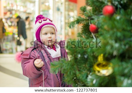 Adorable girl in winter hat and jacket near christmas tree in store