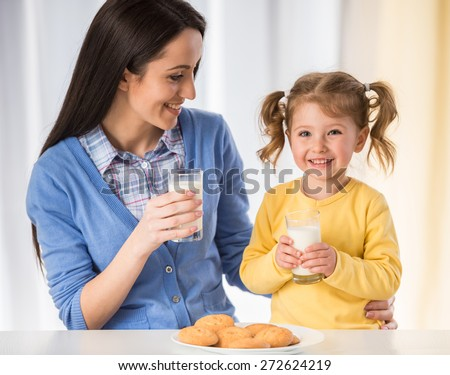 Adorable girl is having an healthy snack with cookies and milk with her mother. - stock photo