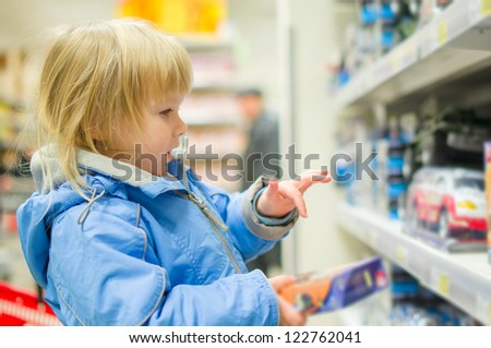 Adorable girl look toy cars and trucks on shelves in supermarket