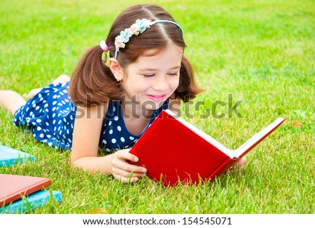 Adorable girl lying on grass and reading a book - stock photo