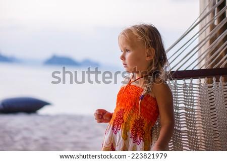 Adorable girl near hammock on tropical beach on sunset - stock photo